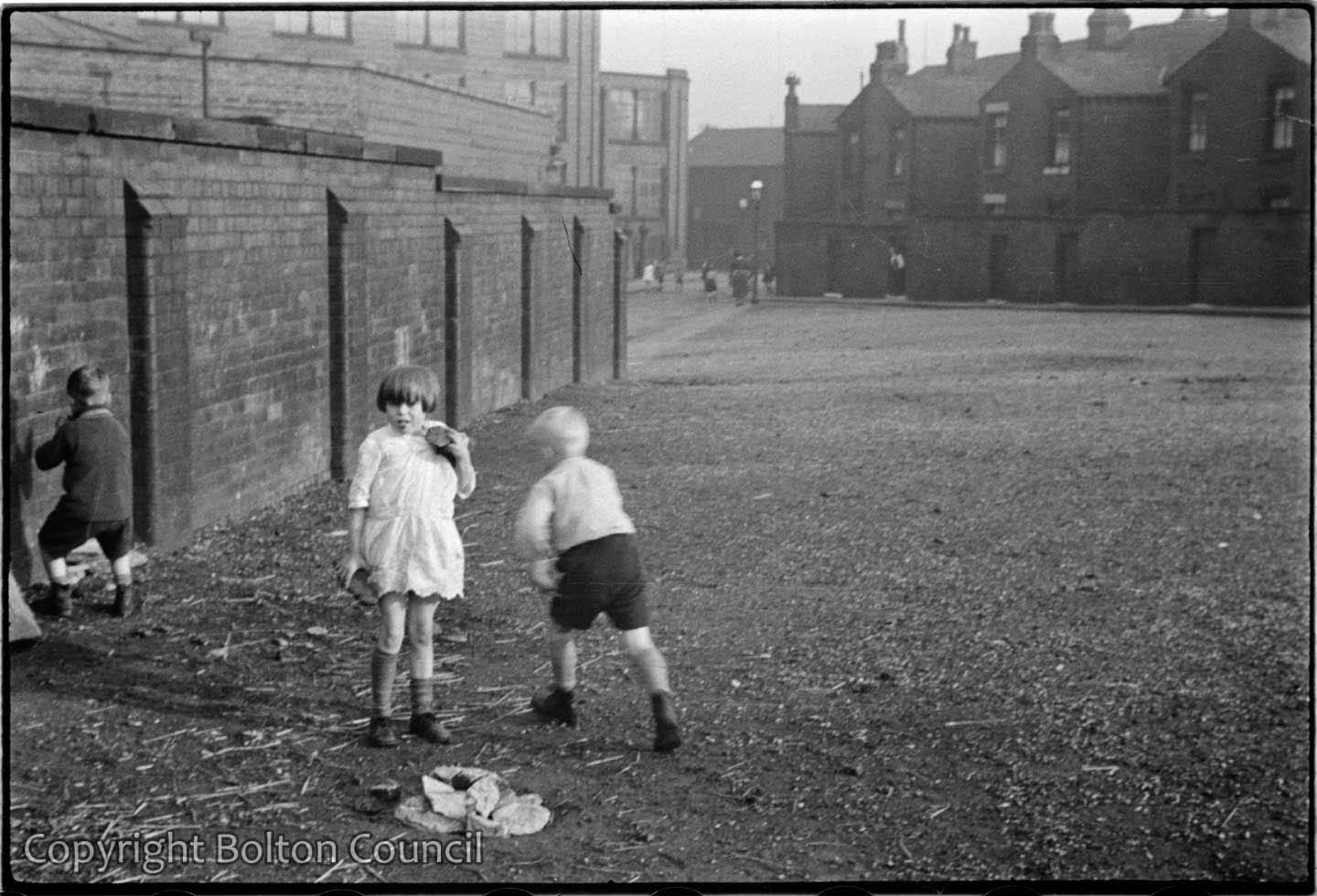 Children play on open land by Snowden St.