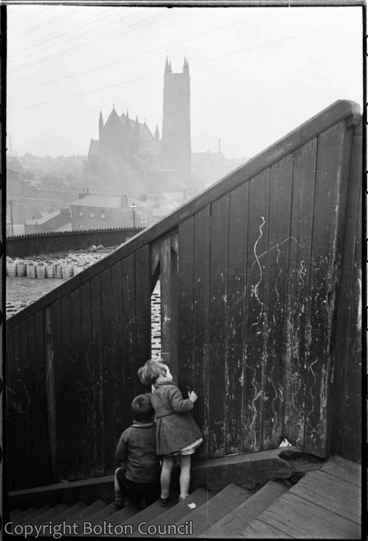 Children peeping through a fence
